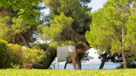 sustain : Middle age woman doing yoga on green grass. Sportive woman doing morning exercises on green grass near the sea. Yoga for women. Female doing yoga pose