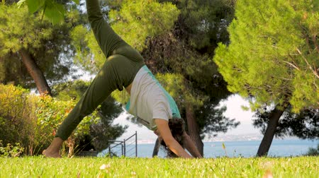 sustain : 30 years old woman doing fitness exercises on grass in park. People taking care of their mental and physical health out in nature. Physical exercises on fresh air on front yard, backyard