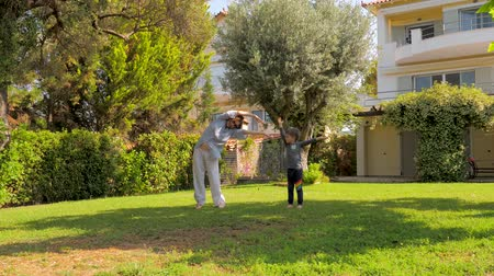 sustain : Little boy having fun while visiting grandmother. Healthy lifestyle concept. Happy childhood concept. Cheerful boy jumping with young grandmother on backyard. Summer vacations, holidays
