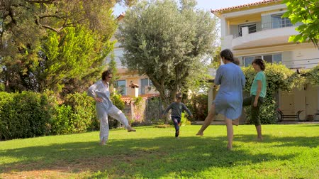 sustain : Three generations having fun while doing exercises on green grass in the garden. Adults and children care about their health. Doing yoga fitness exercises on the villa near the sea