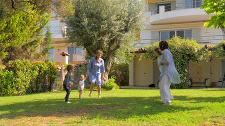 sustain : Happy family jumping in slow motion on front yard of luxury house, villa. Summer holidays concept. Summer vacation with family, Healthy recreations and sports on fresh air