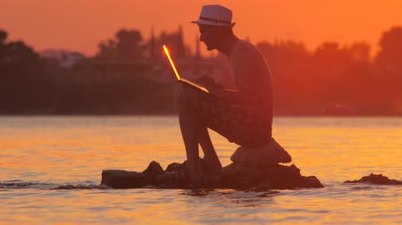 prestigious : Man with laptop in the sea. Male with gadget sitting on the stone in the ocean, sea. Man working on laptop with sunset, sunrise on background. Occupation background. Making money online Stock Footage