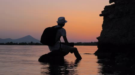 захват : Tourist taking a rest on the stone in the sea. Hipster sitting on the rock in the sea at twilight. Male in hat with backpack looking at sunset on seashore. Non-urban scene. Summer vacation.