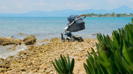 nárazník : Baby vehicle near sea water in Greece. Healthy air near the sea for baby. Toddler transport with seascape on background. Baby stroller on seashore. Baby sleeping in stroller at seaside