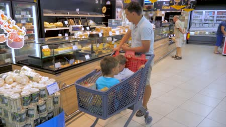 interesse : ATHENS, GREECE - JULY 10 2019: Fatherhood concept. Shopping background. Children sitting in shopping cart. Father moving around supermarket with two kids sitting in shopping cart. Choosing products