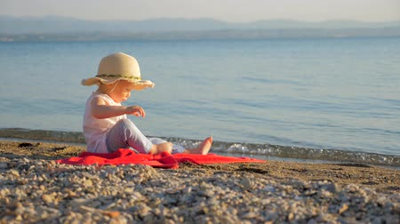 gaining : Lovely baby girl sitting on seashore. Little tourist sitting on red towel and looking on seascape. Summer time or recreations background. Family resort concept. Supportive environment. Autumn vacation