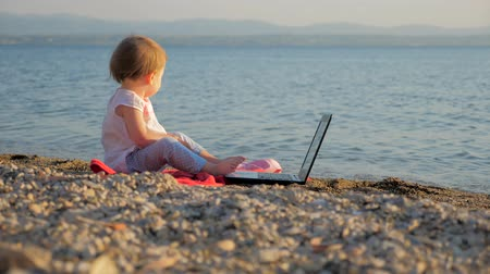 favori : Toddler sitting with notebook on seashore. New generation of people who combine work and vacation. Preschool background. Revolution in education. Developing creativity. New education system background