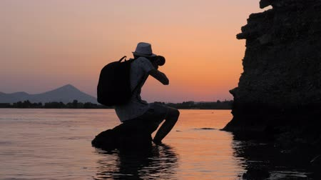 brotos : Artist taking photo for stocks. Young male photographer taking best photo during sunset. Photographer travels and takes pictures. Traveler taking picture and video for stocks