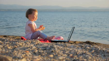 favori : Baby girl sitting with notebook on seashore. New generation of people who combine work and vacation. Creativity and school education. Evolution and revolution at education. Successful freelancer idea