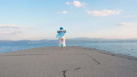 cloud scape : Barefoot kid running along the pier waving his hands happily. Blue umbrella in childs hands on blue sea background. Boy with umbrella moving to camera from lighthouse. Travel concept. Little tourist Stock Footage