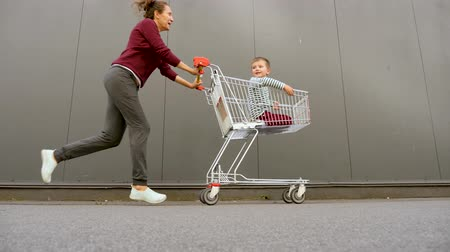 hiány : Culture of consumption. Shopping background. Zero waste background. Considered purchases concept. Cheerful siblings sitting in the shopping cart while father pushing it. Discount, big sales.