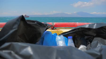 greenpeace : Plastic garbage packed into bag on ship in sea. Plastic from the sea on seascape background. Ship on the horizon while Garbage in cellophane package on the boat, ship. Plastic taken from the sea.
