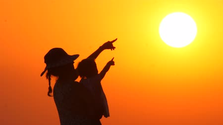 sezgi : Mother in hat with child looking and pointing at the sunset. Baby on mothers hands on orange sky background. Silhouettes of female with toddler on sunset background. Happy family Stok Video