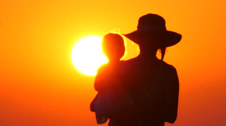 sezgi : Silhouettes of mother and child in her arms on the background of sunset sky. One parent family. Relationships, feelings in family. Motherhood and childhood background. Human and nature