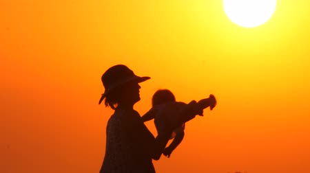 ayrılmak : Mother plays with daughter on the beach during sunset. Happy parenting concept. Abstract background. Summer vacation with child. Happy father with cheerful kid on hands with sunset background