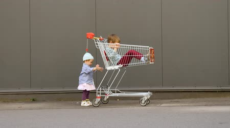 hiány : Little girl pushing shopping cart with brother sitting in it. Children entertainments while waiting for parents from shopping. LIttle hipster with shopping cart near supermarket. Conceptual.