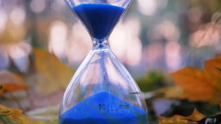 motivo : Sand clock with blue sand. Ten minute sand clock on autumn street background. Time concept. Continued progress of existence, events in the past, present, and future. Time is running. Lifestream idea Stock Footage