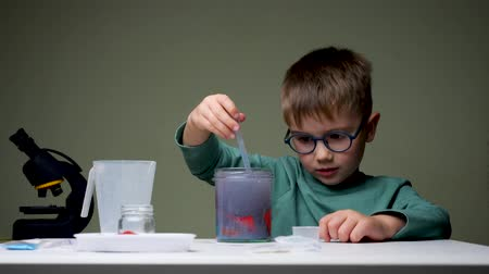 prodigio : Boy in glasses doing experiment. Young scientist mixing up licquid for experiments. Preschooler playing indoor. Home laboratory background Filmati Stock