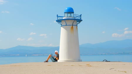 durum : Freelancer works on seaside near lighthouse in Greece. Easy to find a job. Job search near the sea. Man sitting with laptop near lighthouse on quayside. Freelancing background.