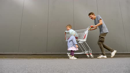 liste : Preparation time concept. Healthy children, mental health. Psycholody, pediatrics background. Preparation for Christmas time. Father driving the son into shopping cart, while daughter following them Stok Video