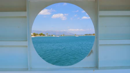 kırpma : City summer landscape view of Greece seen from inside a ship cabin with round peep-hole window. Round window in a shabby wall with brush marks and a sea view clipping path included