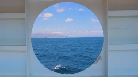 Summer seascape from round window of the yacht. Water transport. Travel concept. View of the sea from the cabin of a cruise liner. View of the sunset and the ocean through the porthole of the ship
