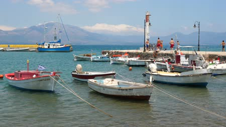 Fishing boats near the pier on Greek island. Traveling concept. Tourism background. Sailing boats with mountains on background.