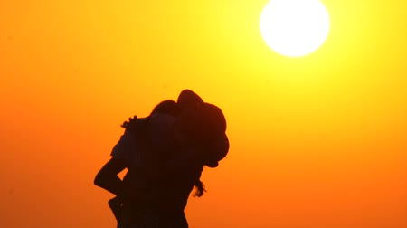 Graceful mother with child. Baby on mothers hands on sunset background. Silhouettes of parent with child on sunset background. Happy family. One child family. Single parent family.
