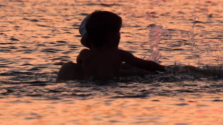Parent and son in the sea with sunset reflecting in the water. Family tours, trips. Travel to Europe. Summer vacation background. Travel trend concept. Original travel. Unique places, locations Wideo