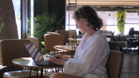 Female in white clothes working on laptop at cafe. Work while traveling. Business woman searches informaion, updates application, checks email at cafe. Remote office job