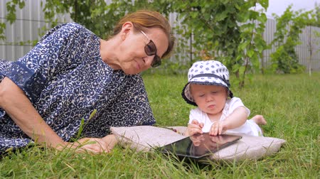 nanny : Kid with nanny watching cartoons. Cartoons on tablet watched outdoor. Girl lying on grass. Childhood, babyhood concept. Toddler with nanny outdoor. Grandmother with grandchild lying on green grass