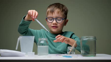 Childhood scientist Learning in the chemistry laboratory. Boy, student learning and doing a chemical experiment and holding test tube in hands in science class on the table. Education concept