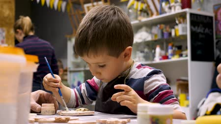 описание : Art school. Boy decorate gift with paintbrush. Drawing lesson. Art workshop. Little painter. Boy decorating clay product with great interest. Leisure activity for child. Kid preparing present.