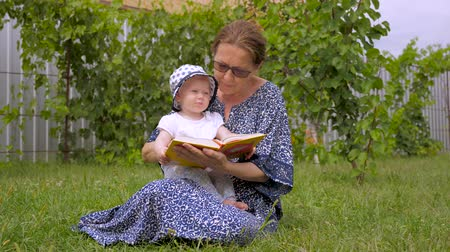 Baby girl with nanny spending time outdoor. Grandmother with toddler sitiing on green grass. Reading book on fresh air. Toddler on fresh air. Happy childhood background.