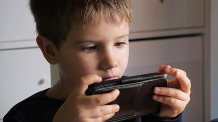 Boy playing video game on mobile phone. Young hacker. Cyber security background. Child and gadget. Facial expression of child with gadget. Video game on mobile phone