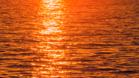 Scenic seascape with sunset reflecting in seawater. Passer-by with notebook walking past. Hot magma color palette. Unusual seascape during sunset. Seawater reflects sunset. Reflected sun in seawater Wideo