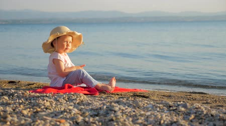 Seascape with baby eyes. Little girl sitting on the coast and looking on seascape. Summer vacation background. Childhood concept. Travel agency background. Tourists places. Wideo