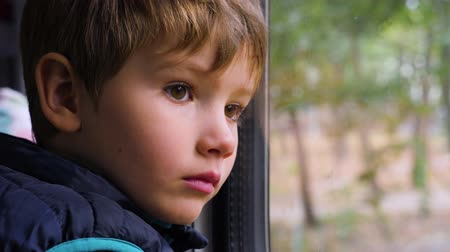 Sad young passenger. Close-up shot of a little curious boy looking out of the window in train. Facial expression. Bad day. The boy looks through window while travel. Facial emotions of little traveler