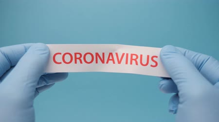 Coronavirus background. Hands in medical gloves hold a piece of paper with coronavirus printed on it.