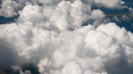 Flying in a plane through the fluffy, snow-white clouds. Spectacular view from the window of an airplane. Aircraft flies into a cluster of beautiful clouds. Nature background