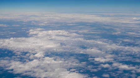 Traveling by air above clouds. View through an airplane window. Flying over the Mediterranean Sea through cirrus and cumulus clouds and little turbulence, showing Earths atmosphere