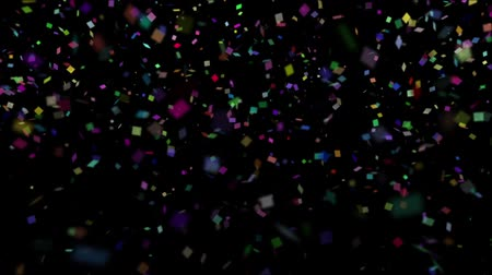 Colored pieces of confetti fall against a black background. Wideo