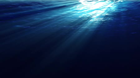 Underwater scene with sunrays shining through the waters glittering and moving surface. Looping.