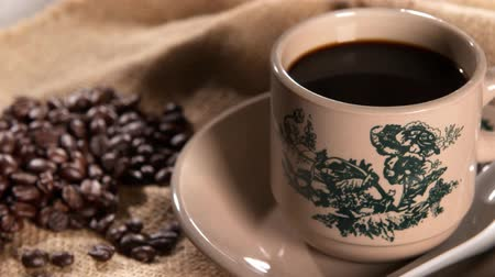 fincan tabağı : Traditional oriental Chinese kopitiam style dark coffee in vintage mug and saucer with coffee beans. Fractal on the cup is generic print. 4k footage panning. Stok Video