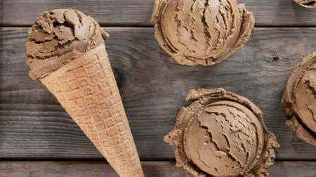 geçiştirmek : Top view cocoa ice cream in waffle cone on old rustic vintage wooden background. 4k footage video. Stok Video