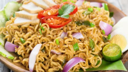 mi : Malaysian style maggi goreng mamak  or spicy fried curry instant noodles.  Asian cuisine, ready to serve on wooden dining table setting.  Ready to serve on wooden dining table setting. 4k footage video. Stock Footage