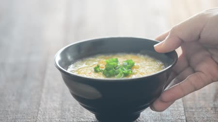 turn table : Serving a bowl rice congee on dining table, natural lighting background. Stock Footage