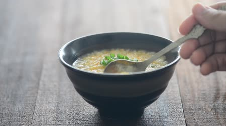 congee : Spoon scooping Chinese rice congee on dining table, natural lighting background. Stock Footage