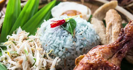 chili : Nasi kerabu or nasi ulam, popular Malay rice dish. Blue color of rice resulting from the petals of butterfly-pea flowers. Traditional Malaysian food, Asian cuisine, 4k footage video. Stock mozgókép