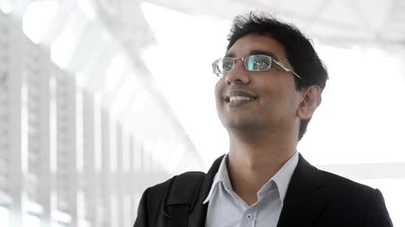 стенд : Portrait of a good looking smiling Indian businessman standing at modern building, with natural light.